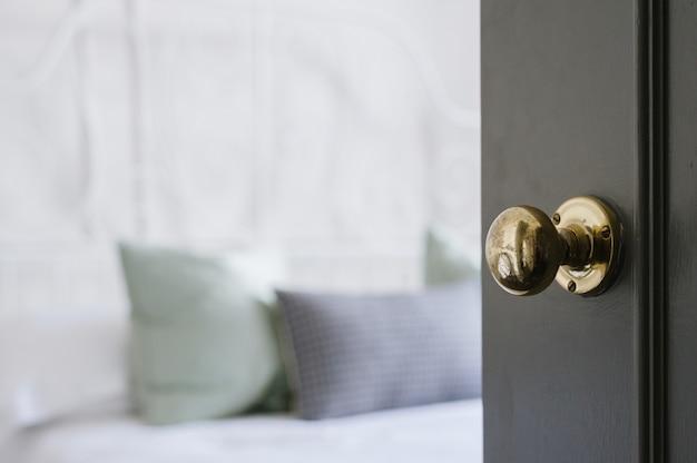 Closeup shot of a gold door knob on a black door Free Photo