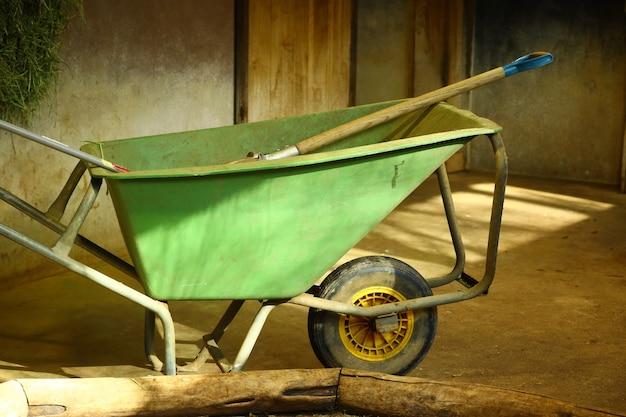 Closeup shot of a green wheelbarrow in a room Free Photo