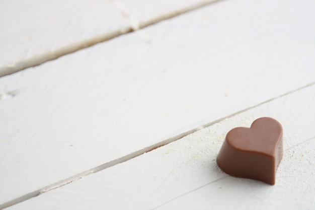 Colpo del primo piano di una caramella di cioccolato a forma di cuore su una tavola di legno bianca Foto Gratuite