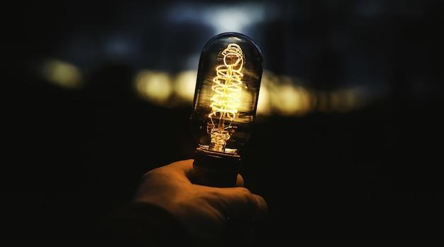 Colpo del primo piano di una mano umana che tiene una lampada Foto Gratuite