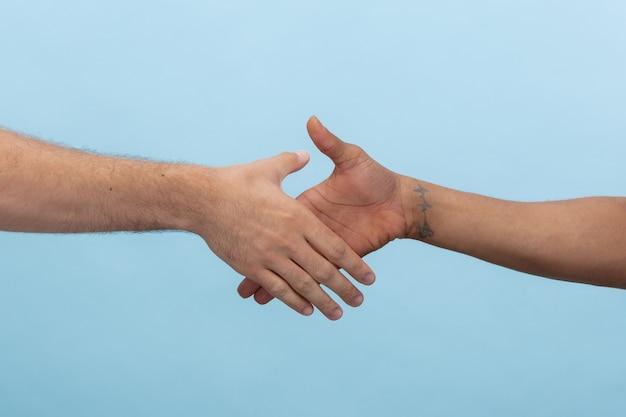 Colpo del primo piano dell'uomo che tiene le mani isolate sull'azzurro Foto Gratuite