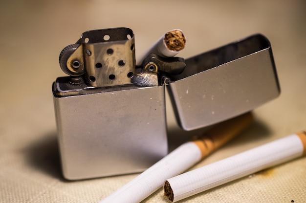 Colpo del primo piano di un accendino e sigarette - smettere di fumare concetto Foto Gratuite