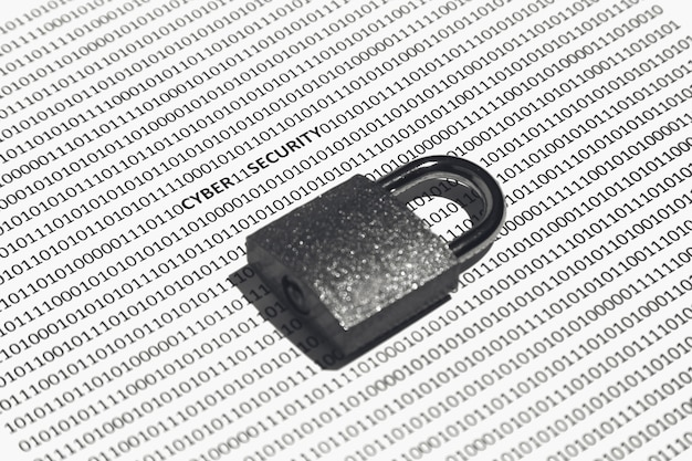 Closeup shot of a lock on a white surface with binary code on it - concept of cybersecurity Free Photo