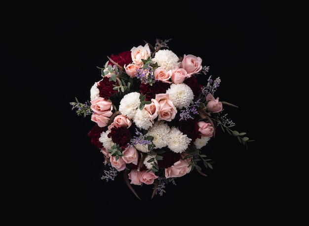 Closeup shot of a luxurious bouquet of pink roses and white, red dahlias on a black background Free Photo