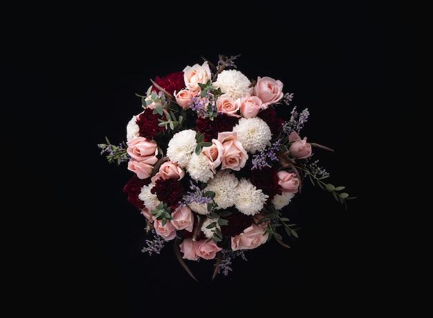 Colpo del primo piano di un lussuoso bouquet di rose rosa e dalie bianche e rosse su sfondo nero Foto Gratuite
