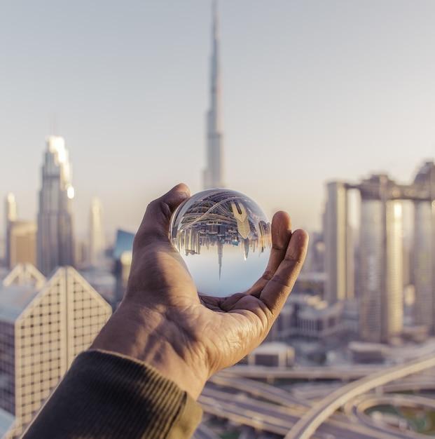 Colpo del primo piano di una mano maschio che tiene una sfera di cristallo con il riflesso della città Foto Gratuite