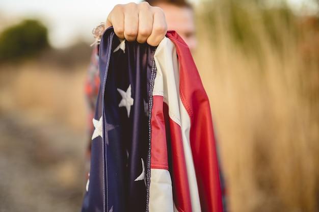 Colpo del primo piano di un maschio che tiene la bandiera degli stati uniti Foto Gratuite