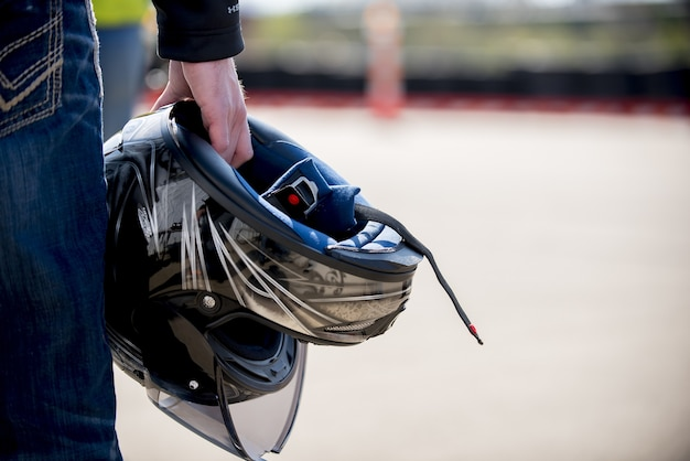 Closeup shot of a male holding his motorcycle helmet with a blurred distance Free Photo