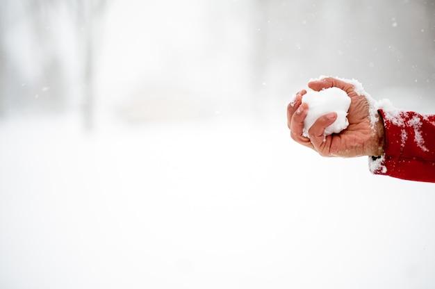 Colpo del primo piano di un maschio che tiene una palla di neve Foto Gratuite