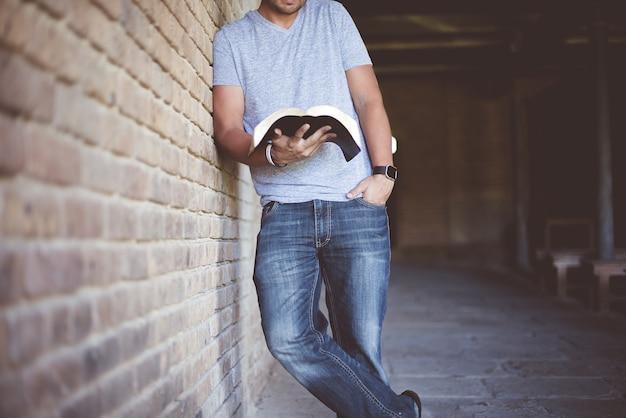 Colpo del primo piano di un maschio appoggiato a un muro durante la lettura della bibbia Foto Gratuite