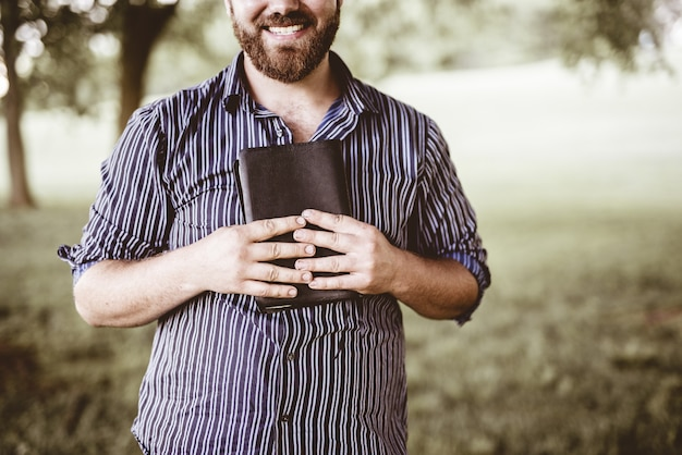 Closeup shot of a male smiling and holding the bible with a blurred background Free Photo
