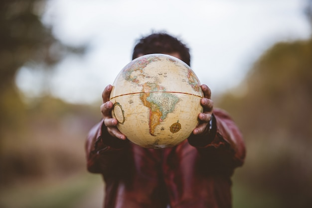 Closeup shot of a male wearing a leather jacket holding a globe in front of him Free Photo