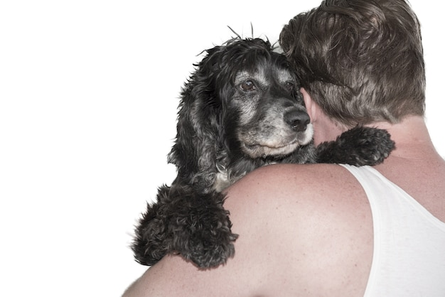 Colpo del primo piano di un uomo che abbraccia un cane nero dietro su bianco Foto Gratuite