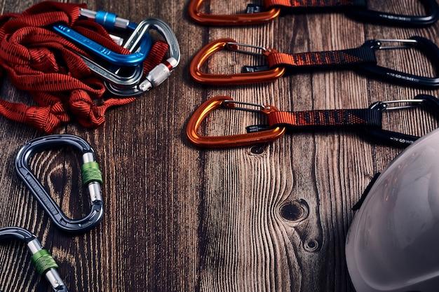 Colpo del primo piano di molti moschettoni da arrampicata colorati e nodi su una superficie di legno Foto Gratuite