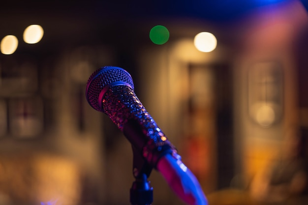 Closeup shot of a microphone on a blurred space with bokeh lights Free Photo