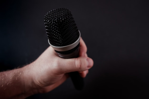 Closeup shot of a microphone in the hand of a person on black Free Photo