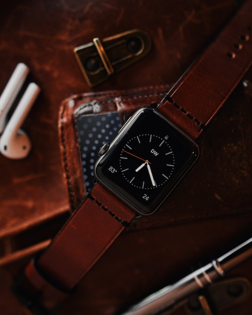 Closeup shot of a modern cool black digital watch with a brown leather strap Free Photo