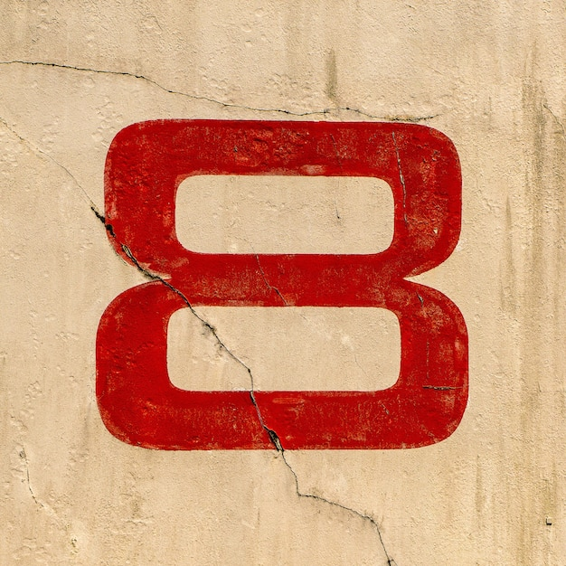 Closeup shot of the number 8 painted on a wall in red Free Photo