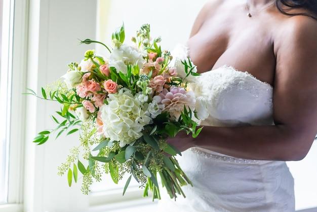 꽃 꽃다발을 들고 흰 드레스 신부의 근접 촬영 샷 무료 사진