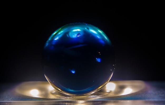 暗い背景で照らされた表面の上に濃い青の大理石のクローズアップショット 無料写真