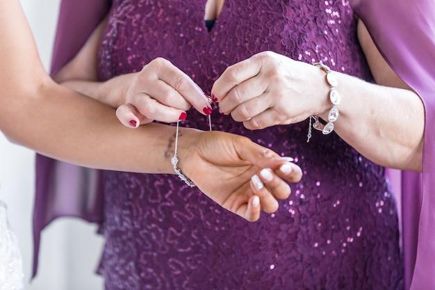 여성의 근접 촬영 샷은 다른 여성에 의해 그녀의 보석을 씌우는 데 도움을 받고 무료 사진