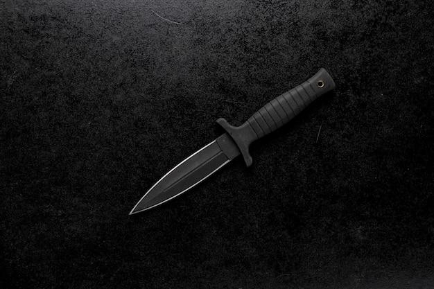 검정색 배경에 고정 된 날카로운 칼의 근접 촬영 샷 무료 사진
