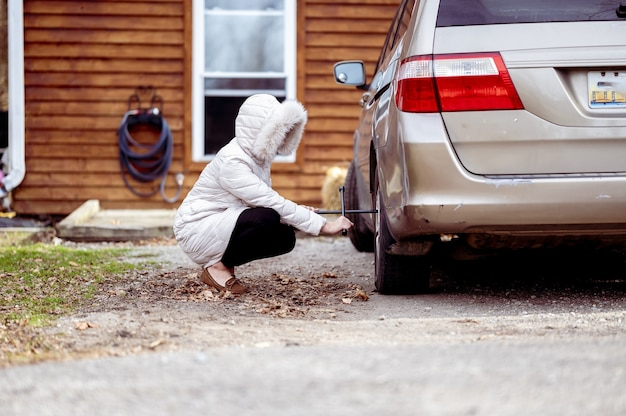 자동차 바퀴를 수리하는 여자의 근접 촬영 샷 무료 사진