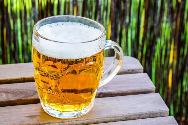 木製の表面に冷たいビールのグラスのクローズアップショット 無料写真