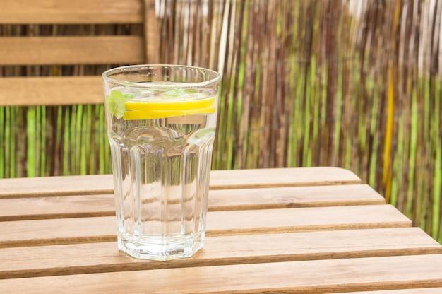 木製のベンチにレモンとミントと水のガラスのクローズアップショット 無料写真
