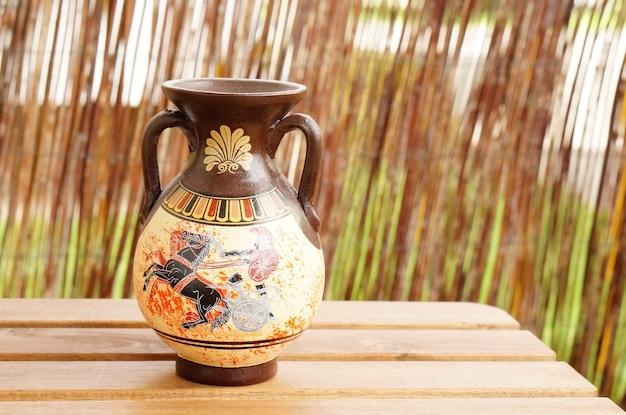 Снимок крупным планом греческой вазы на деревянном столе Бесплатные Фотографии