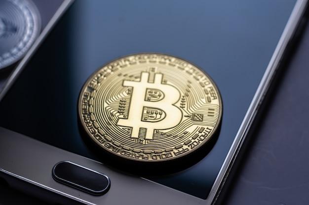 携帯電話の上に置かれた大きなコインのクローズアップショット 無料写真