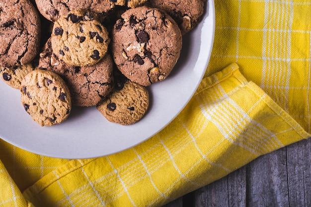 白いプレートにたくさんのチョコレートチップクッキーのクローズアップショット 無料写真