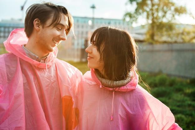 ロマンチックにお互いを見てピンクのプラスチック製のレインコートを着た男性と女性のクローズアップショット 無料写真