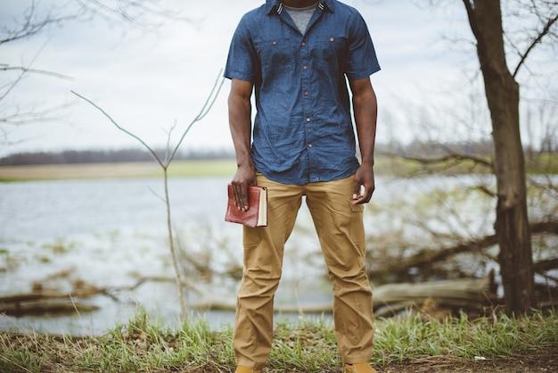 立っている間、聖書を持っている男性のクローズアップショット 無料写真