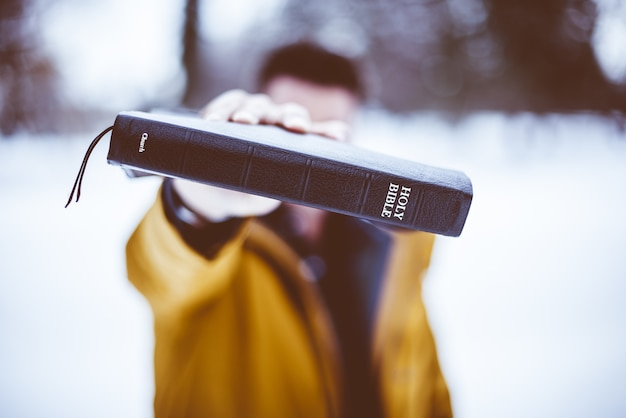 Снимок крупным планом мужчины, держащего библию в сторону Бесплатные Фотографии