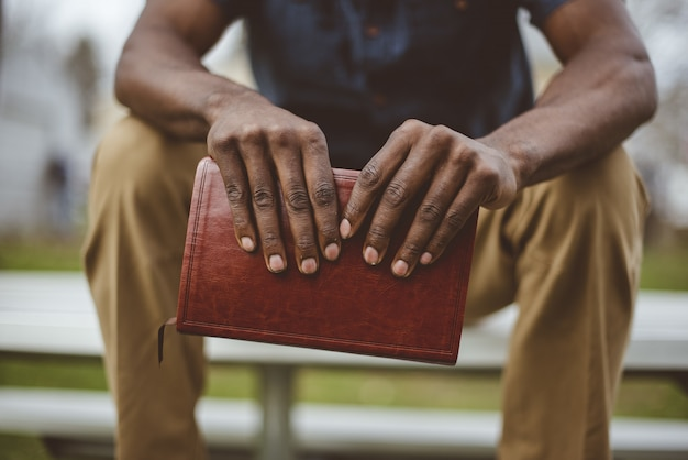 Съемка крупного плана мужчины сидя в парке пока держащ библию Бесплатные Фотографии