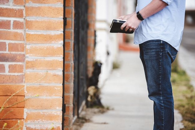 Съемка крупного плана мужчины стоя около здания пока держащ библию Бесплатные Фотографии