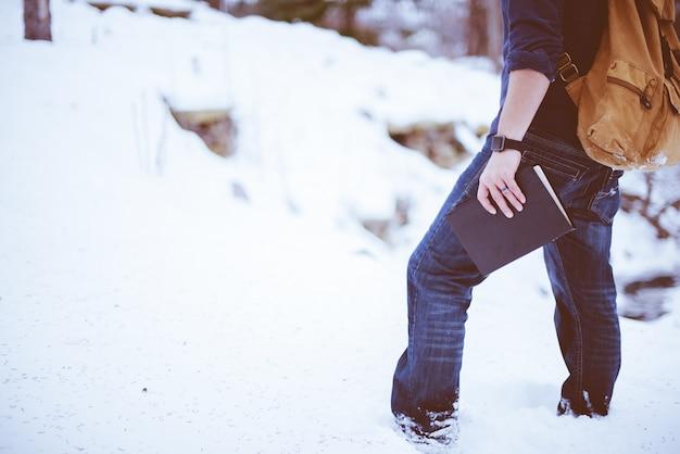Съемка крупного плана мужчины нося рюкзак стоя в снеге и держа библию Бесплатные Фотографии
