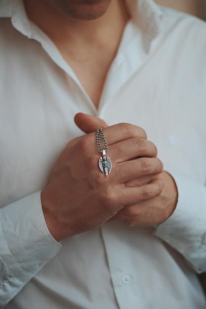 銀の男性のネックレスを保持している白いシャツを着ている男性のクローズアップショット 無料写真