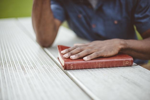 Макрофотография выстрел из мужчины с его рукой на библии на деревянном столе Бесплатные Фотографии