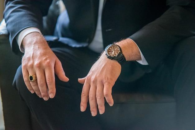 スーツを着た男性のクローズアップショット、より正確には、彼の手、指輪、腕時計 無料写真