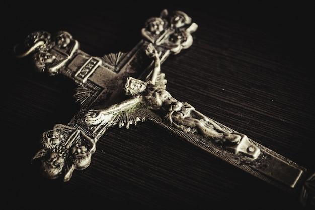 Металлический крест на черном деревянном столе крупным планом Бесплатные Фотографии