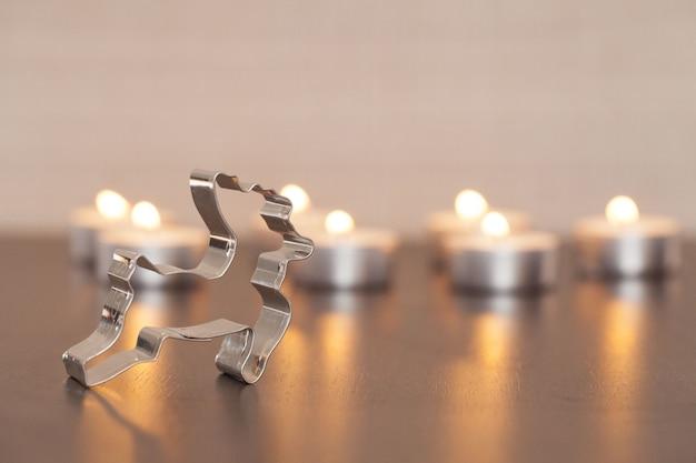 금속 사슴 장식과 배경에 흐리게 촛불의 근접 촬영 샷 무료 사진