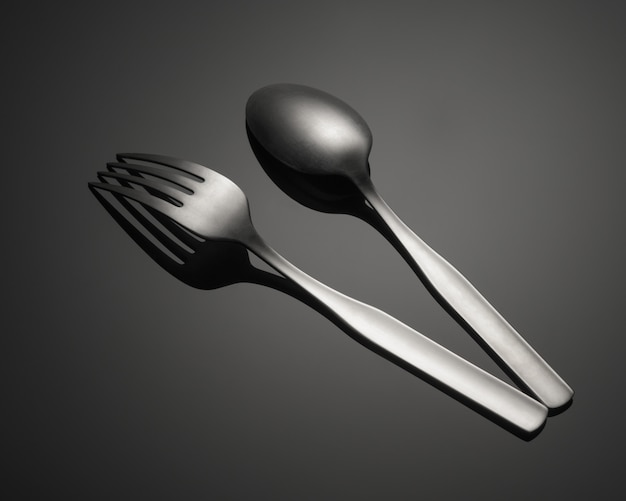 金属のフォークと灰色のテーブルに分離されたスプーンのクローズアップショット 無料写真