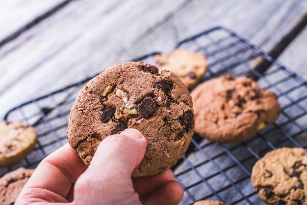 ぼやけた背景にチョコレートチップクッキーを持っている人のクローズアップショット 無料写真
