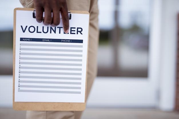 자원 봉사자 가입 시트를 들고 사람의 근접 촬영 샷 무료 사진