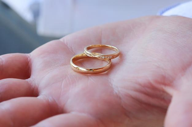 2つの金の結婚指輪を持っている人のクローズアップショット 無料写真