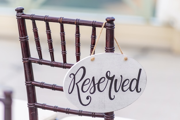 Снимок крупным планом зарезервированного знака, висящего на стуле на свадебной церемонии Бесплатные Фотографии