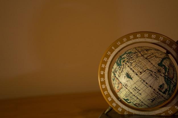 베이지 색에 회전하는 지구본의 근접 촬영 샷 무료 사진
