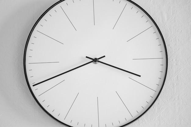白い壁に白と黒の時計のクローズアップショット-時間の概念 無料写真